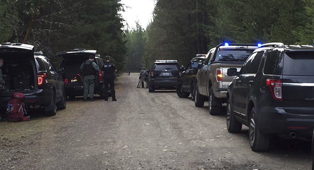 Police vehicles line the road near a rural property near Belfair, Washington, February 26, 2016 in this handout photo provided by Mason County Sheriff's Office in Shelton, Washington