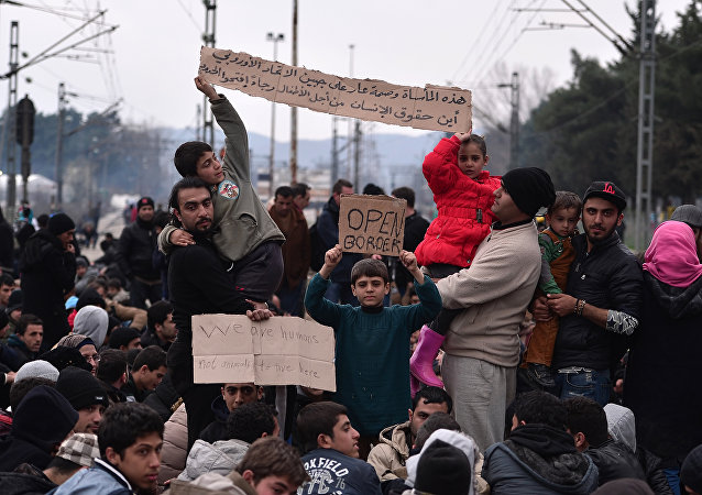 Syrian and Iraqi refugees trapped at the Greek-Macedonian borders demonstrate shouting 'open the border' as they block the train tracks on February 28, 2016