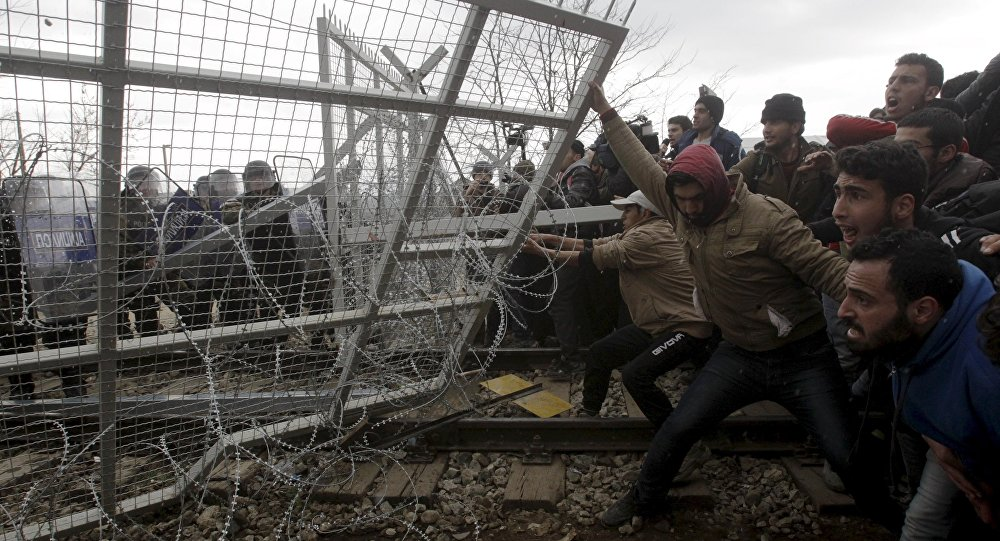 Stranded refugees and migrants try to bring down part of the border fence during a protest at the Greek-Macedonian border, near the Greek village of Idomeni, February 29, 2016