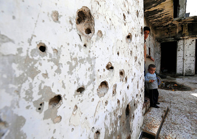 In this picture taken Friday, Feb. 26, 2016, Syrian boys are seen inside their destroyed house at neighborhood of Baba Amr in Homs, Syria