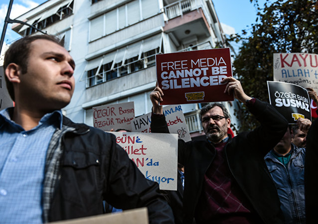 Turkish protesters hold placards outside the headquarters of Bugun newspaper and Kanalturk television station during a demonstration in Istanbul against the Turkish government's crackdown on media outlets (file photo)