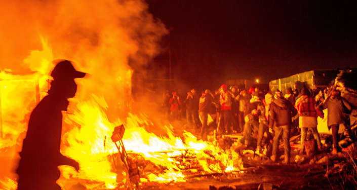 Migrants stand next a fire burning shacks, in the southern part of the so-called Jungle migrant camp, as half of the camp is being dismantled, in the French northern port city of Calais, on March 1, 2016.
