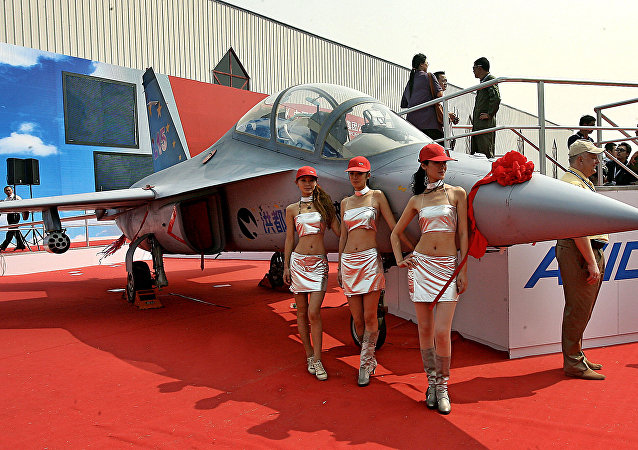 Models pose next to a Chinese-made L15 advanced trainer jet fighter