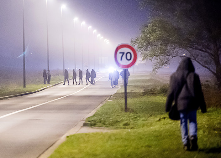 Migrants walk on a road towards the Eurotunnel site in Coquelles, northern France, on October 3, 2015.