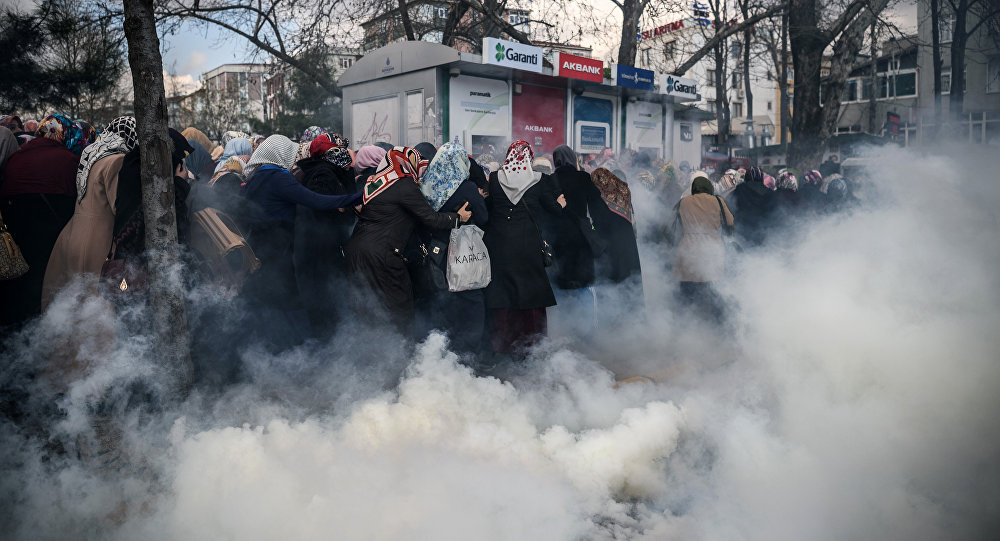 Smoke rises near a group of women as Turkish anti-riot police officers use tear gas to disperse supporters in front of the headquarters of the Turkish daily newspaper Zaman in Istanbul on March 5, 2016, after Turkish authorities seized the headquarters in a midnight raid