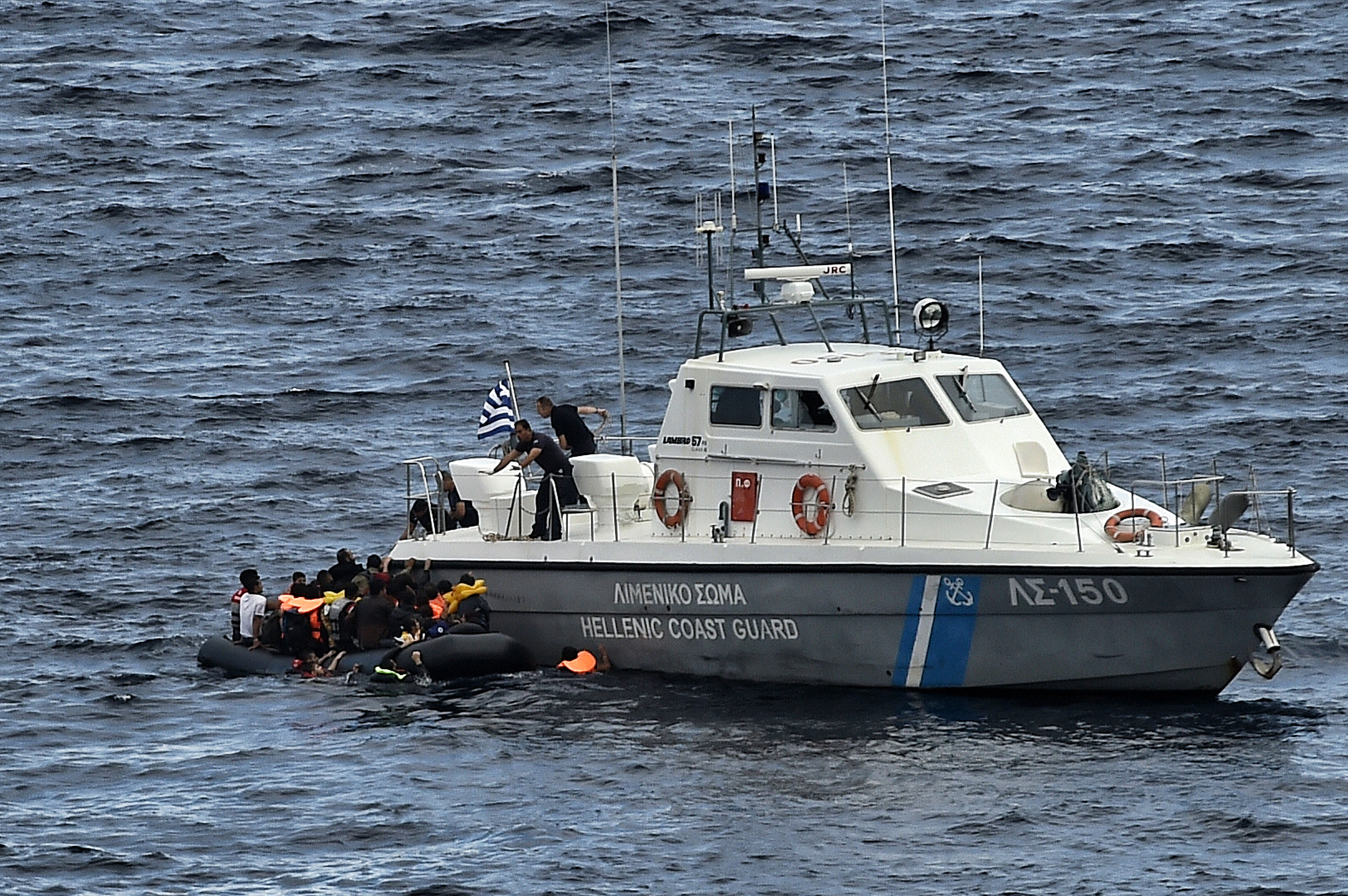 Hellenic coast guard personnel rescue refugees and migrants on a dinghy as they try to reach the Greek island of Lesbos while crossing the Aegean sea from Turkey on September 29, 2015
