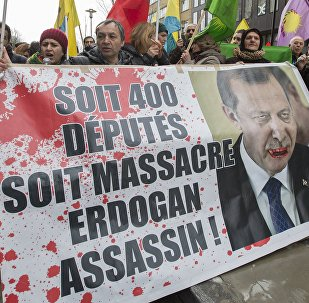 Kurdish people display a picture of Turkish President Tayyip Erdogan during a protest outside an EU-Turkey summit as the bloc is looking to Ankara to help it curb the influx of refugees and migrants flowing into Europe, in Brussels March 7, 2016