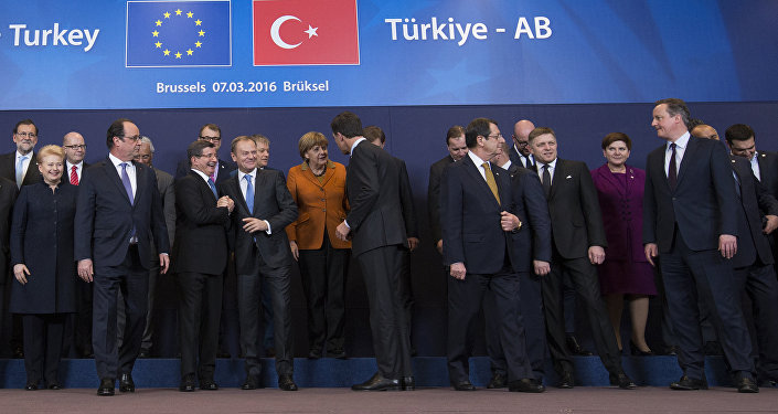 French President Francois Hollande (2nd L front row) looks on as Turkish Prime Minister Ahmet Davutoglu (3rd L) chats with European Council President Donald Tusk (4th L) while posing with European Union leaders during a EU-Turkey summit in Brussels, as the bloc is looking to Ankara to help it curb the influx of refugees and migrants flowing into Europe, March 7, 2016