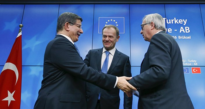 Turkish Prime Minister Ahmet Davutoglu (L), European Council President Donald Tusk (C) and European Commission President Jean Claude Juncker (R) greet each other after a news conference at the end of a EU-Turkey summit in Brussels March 8, 2016.