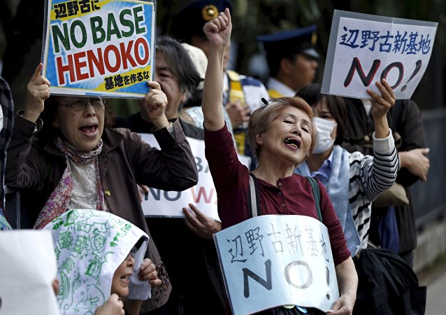 People protesting the planned relocation of the U.S. military base, to Okinawa's Henoko coast, shout slogans at a rally in front of Prime Minister Shinzo Abe's official residence, as a meeting between Okinawa Governor Takeshi Onaga and Abe is held, in Tokyo in this April 17, 2015 file photo
