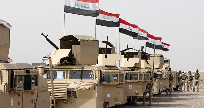 Iraqi security forces ride in vehicles travelling to Mosul