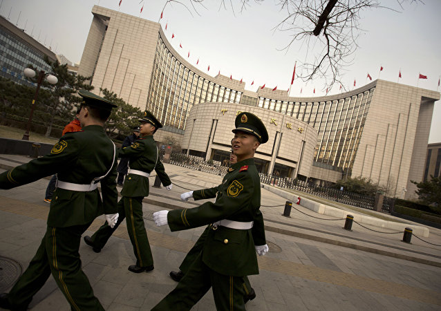 Chinese paramilitary police march past China's central bank, the People's Bank of China, in Beijing, Saturday, March 12, 2016
