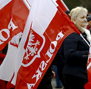 A woman holds the Polish national flag as she takes part in a march demanding their government to respect the country's constitution in Warsaw, Poland, March 12, 2016.
