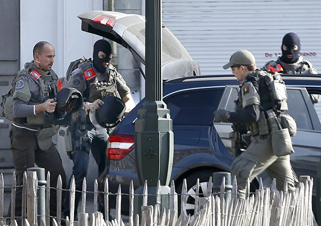 Police at the scene where shots were fired during a police search of a house in the suburb of Forest near Brussels, Belgium, March 15, 2016
