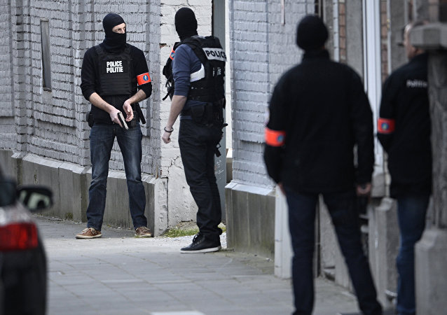 Police officers take position at the site of a shooting in the southern Forest district of Brussels on March 15, 2016