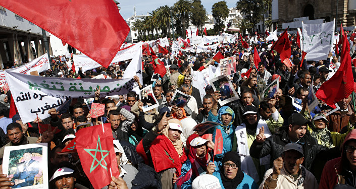 Protesters hold portraits of Morocco's King Mohammed VI and the Moroccan flag as they chant slogans during a rally, in Rabat, Morocco, Sunday, March 13, 2016. Morocco has accused U.N. Secretary-General Ban Ki-moon of abandoning neutrality, objectivity and impartiality during a recent visit to Western Saharan refugee camps in southern Algeria