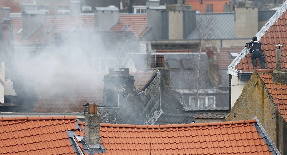 Belgium police officer secures the area from a rooftop at the scene where shots were fired during a police search of a house in the suburb of Forest near Brussels, Belgium, March 15, 2016
