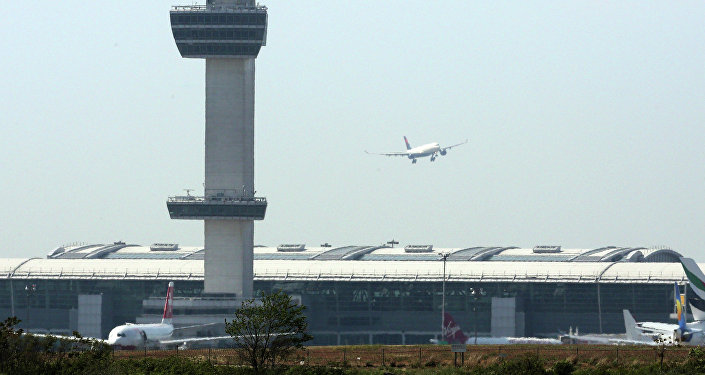 An aircraft flies past the control tower as it prepares to land at New York's John F Kennedy Airport, May 25, 2015