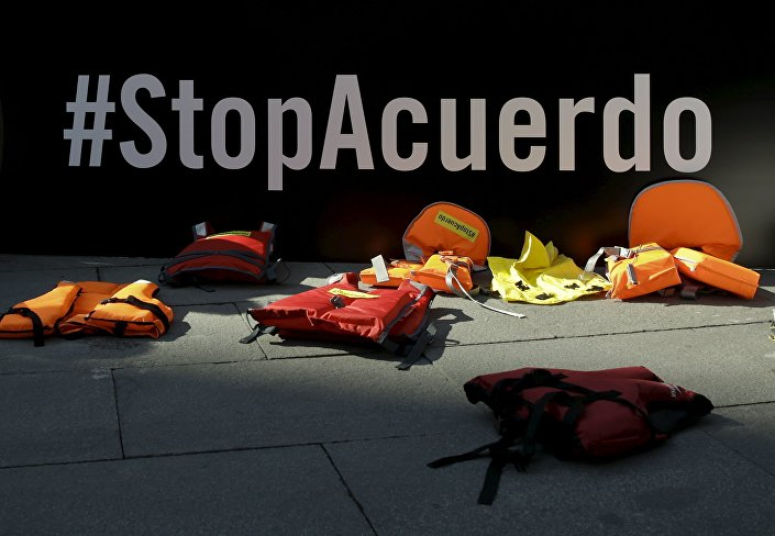 Life vests lie in front of a banner reading Stop the Deal during a protest against the EU-Turkey migrant deal in front of the Spanish foreign ministry in Madrid, Spain, March 16, 2016.