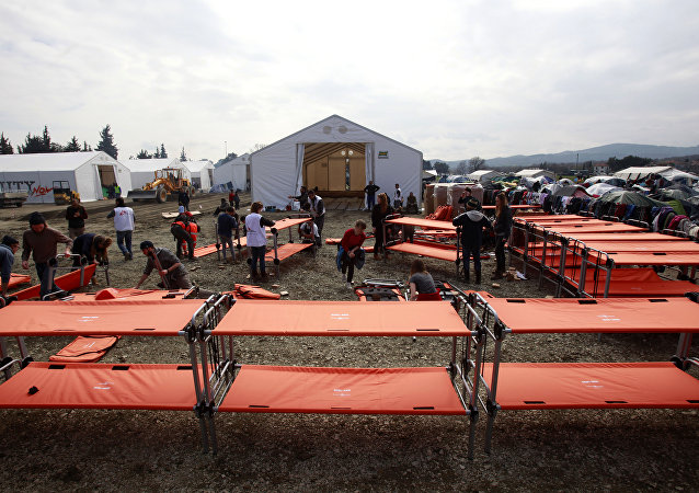 Humanitarian workers prepare new beds for the migrants in the camp at the northern Greek border post of Idomeni, Greece, Friday, March 18, 2016.