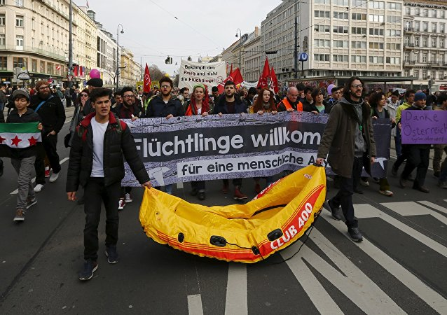 Protesters hold up banners and a rubber boat during a demonstration Refugees Welcome! No to Fortress Europe in Vienna, Austria