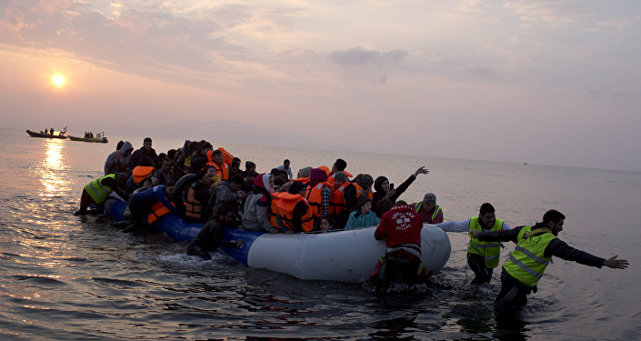 Volunteers help migrants and refugees on a dingy as they arrive at the shore of the northeastern Greek island of Lesbos, after crossing the Aegean sea from Turkey on Sunday, March 20, 2016