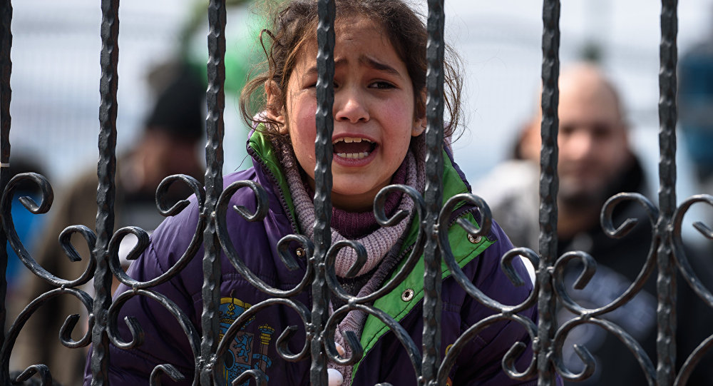 A migrant girl cries as she waits at a Turkish coast guard station at the Dikili district in Izmir, on March 20, 2016, after being catched with other migrants while trying to reach the Greek island of Lesbos from the Bademli village, western Turkey.
