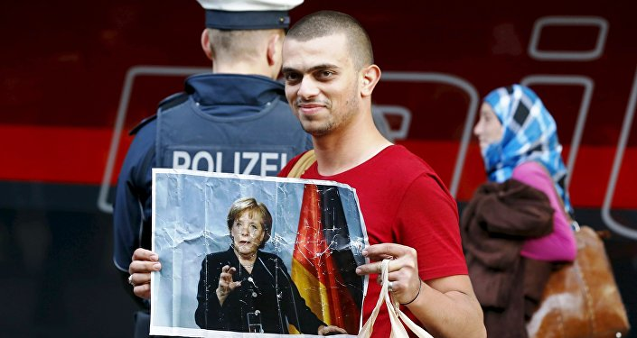 A migrant holds a picture of German Chancellor Angela Merkel after arriving to the main railway station in Munich, Germany, in this September 5, 2015.