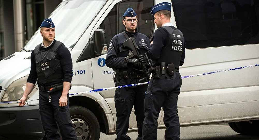 Policemen stand guard at the entrance of a security perimeter set in the Rue de la Loi near the Maalbeek subway station, in Brussels, on March 22, 2016