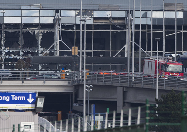 The blown out facade of the terminal is seen as a fire truck drives down the ramp at Zaventem airport, one of the sites of two deadly attacks in Brussels, Belgium, Tuesday, March 22, 2016