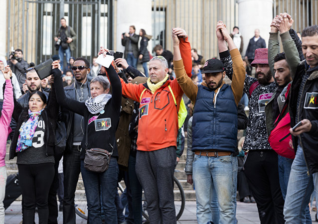 People stand hand in hand in tribute to victims at a makeshift memorial in front of the stock exchange at the Place de la Bourse (Beursplein) in Brussels on March 22, 2016