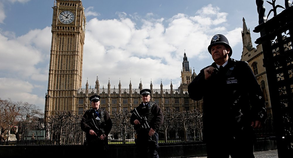 Armed British police officers stand on duty in front of the Elzabeth Tower, better known as Big Ben, outside the vehicle entrance to the Houses of Parliament in central London on March 22, 2016.