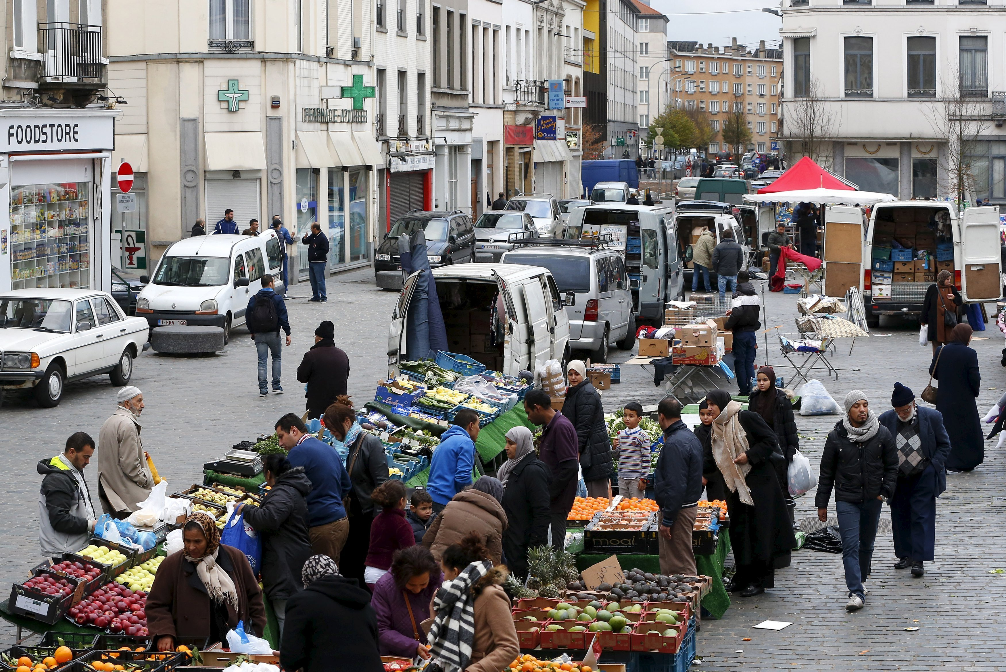 People shop at a market in the neighbourhood of Molenbeek, where Belgian police staged a raid following the attacks in Paris, at Brussels, Belgium November 15, 2015