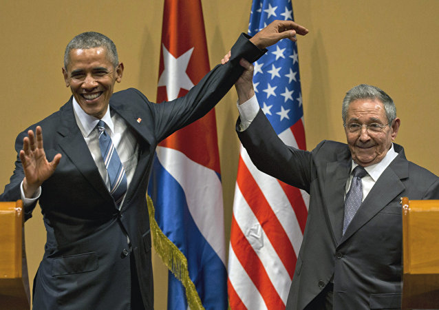 Cuban President Raul Castro, right, lifts up the arm of President Barack Obama at the conclusion of their joint news conference at the Palace of the Revolution, Monday, March 21, 2016, in Havana, Cuba