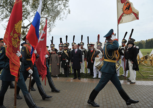 Russian President Vladimir Putin, background center, watching the march of the company of honor guards during celebrations of the 200th anniversary of the Battle of Borodino at the State Borodino Military and Historical Museum-Reserve, September 2, 2012.