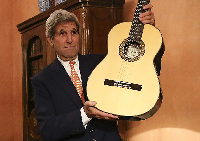 US Secretary of State John Kerry shows at the guitar which was given by Spanish Minister of Foreign Affairs and Cooperation Jose Manuel Garcia Margallo during a meeting in Madrid on October 18, 2015