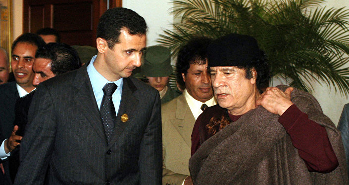 In this March 22, 2005 file photo, Syrian President Bashar Assad, left, talks to Libyan leader Moammar Gadhafi prior the 17th League of Arab States' summit in Algiers, Algeria.