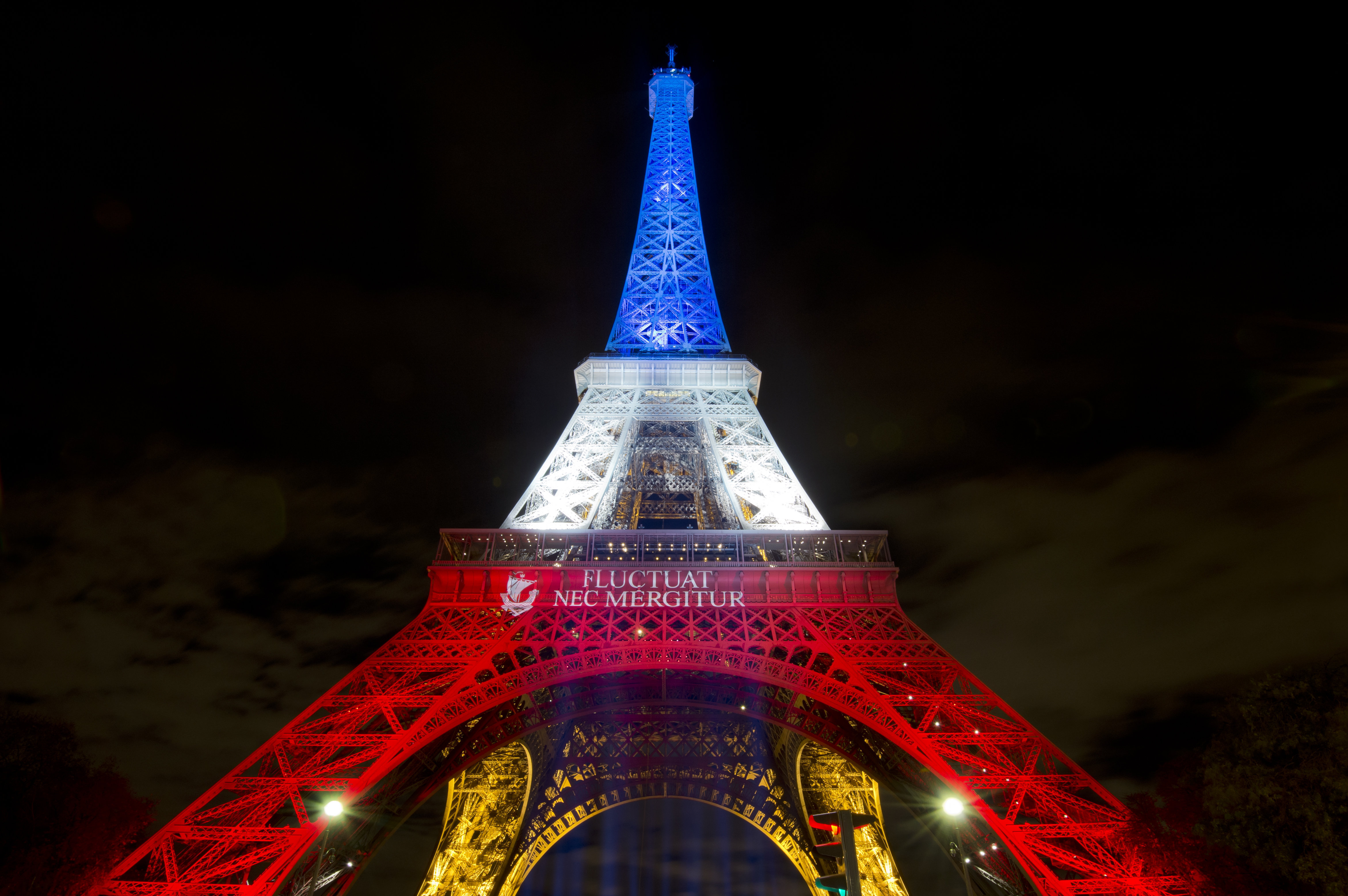 A photo taken on November 17, 2015 in Paris shows the Eiffel Tower illuminated with the colors of the French national flag in tribute to the victims of the November 13 Paris terror attacks.