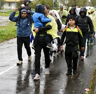 Refugees walk through the pouring rain from a public transport centre to the Lappia-building refugee reception centre in Tornio, northwestern Finland, on September 2015.