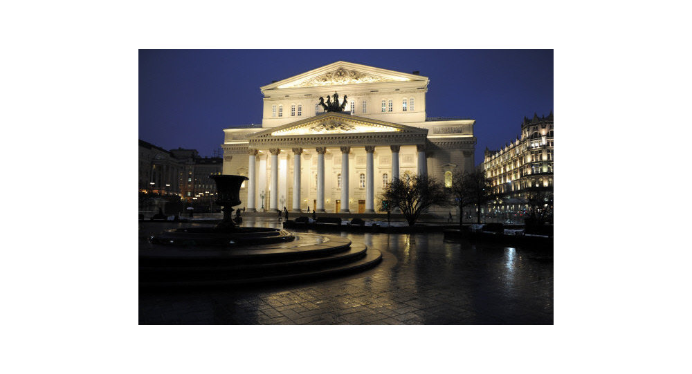 The Bolshoi Theater in Moscow stands illuminated at night.