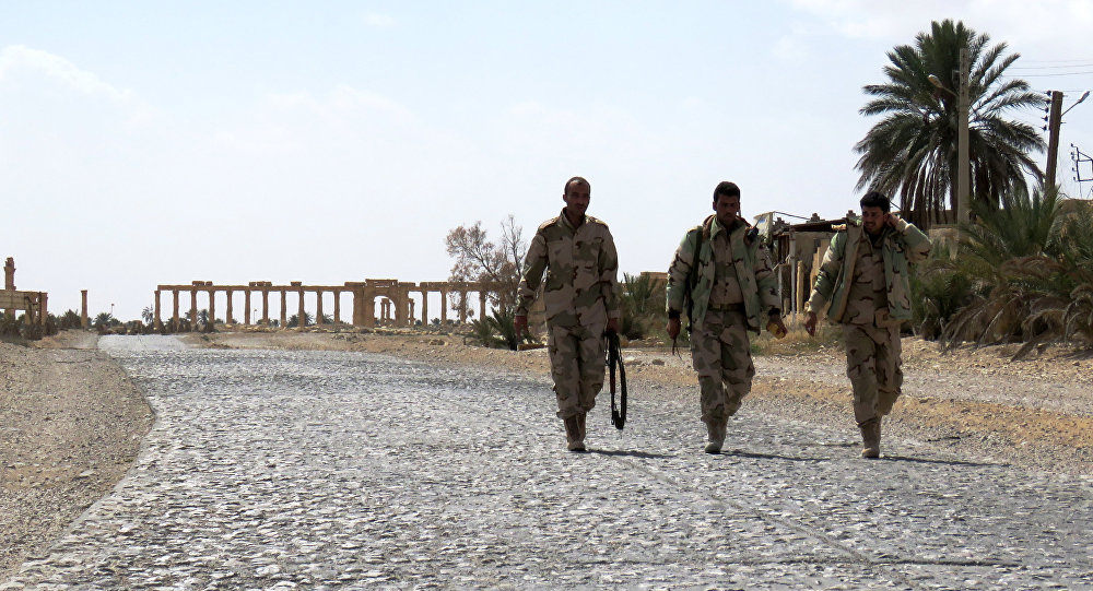 Syrian troops walk in the ancient city of Palmyra after they recaptured the site from the Islamic State (IS) group on March 27, 2016