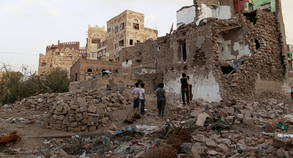Yemeni children look on March 23, 2016 at buildings that were damaged by air strikes carried out by the Saudi-led coalition over the past year in the UNESCO-listed old city of the Yemeni capital Sanaa