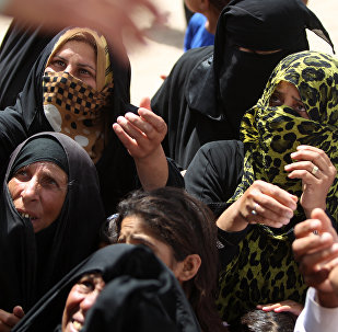 Displaced Iraqi women, who fled Ramadi, the capital of Anbar province, after it was seized by the Islamic State (IS) group, wait to get aid boxes at a makeshift camp for internally displaced persons (IDP) in Ameriyat al-Fallujah, 30 km south of Fallujah on June 6, 2015