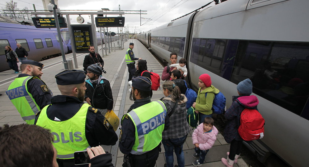 Policemen and a group of migrants stand on the platform at the Swedish end of the bridge between Sweden and Denmark
