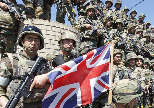 Lebanese army soldiers carry their weapons as they stand during the visit of Britain's Foreign Secretary Philip Hammond to a military air base in Hamat, northern Lebanon March 31, 2016