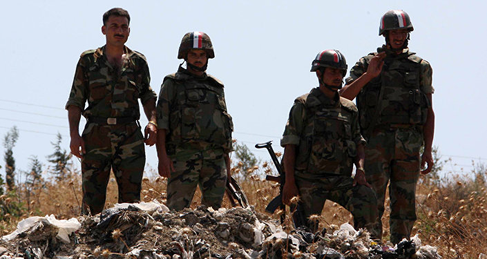 Syrian soldiers stand guard near a mass grave (File)