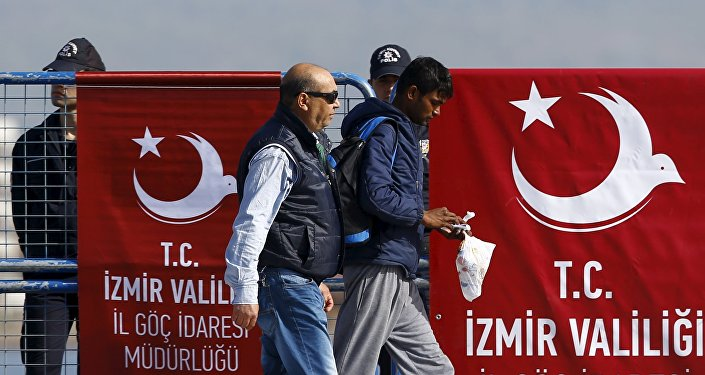 A migrant is escorted by a Turkish police officer as he arrives in the Turkish coastal town of Dikili, Turkey, April 4, 2016