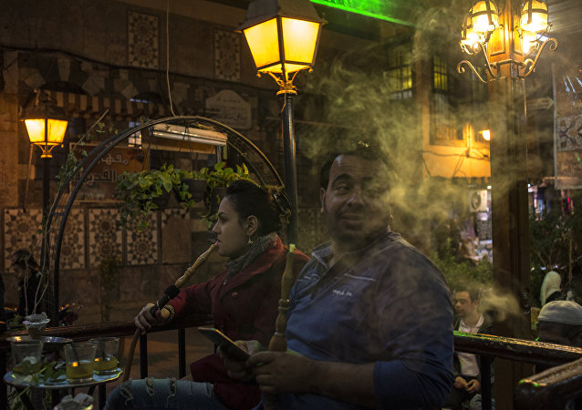 People smoke hookahs in a Damascus cafe