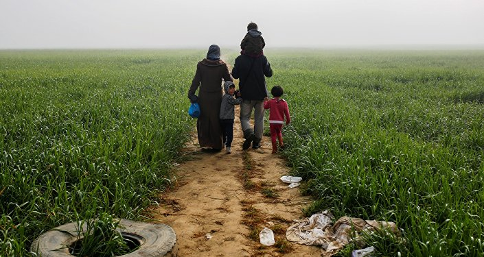 A family walks through a field at a makeshift camp for migrants and refugees at the Greek-Macedonian border near the village of Idomeni, Greece, April 4, 2016.