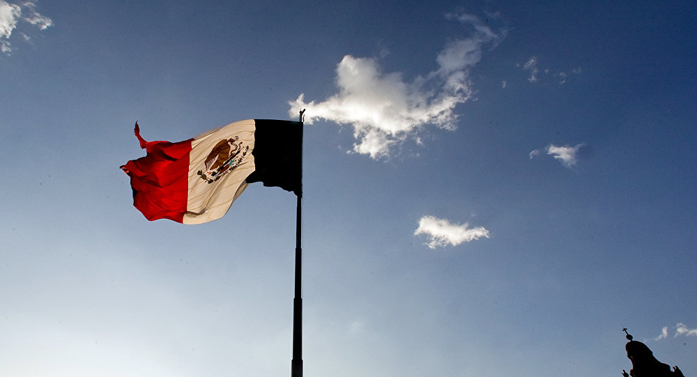 A Mexican flag flutters at the Zocalo square in Mexico City, on April 29, 2009.